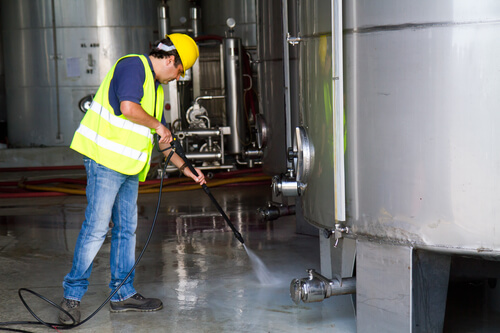 Man cleaning inside of a factory in Calgary with a professional pressure washer.